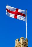 Cross of St George flying from castle ramparts. In England Royalty Free Stock Photo