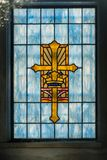 Cross in Stained glass window in church that is gold and blue christianity. Stained glass window in a church cross is gold and blue christianity Stock Photos