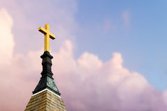 Cross on Steeple in the Sky. Cross atop a steeple with colorful clouds behind royalty free stock images