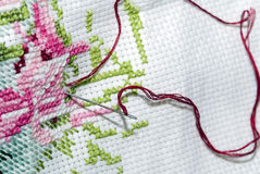 Cross stitch. A cross stitch image with a needle and red yarn stock image
