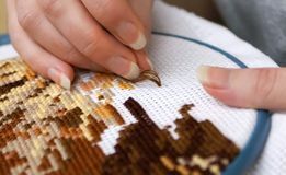 Cross-stitch. Woman's hands embroidering a picture (cross-stitch Stock Photos