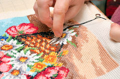 Cross stitch. Woman embroidering a picture of flowers (cross stitch Royalty Free Stock Photography