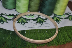 Cross-stitch embroidery frame wooden towel in bright green threa Stock Photos