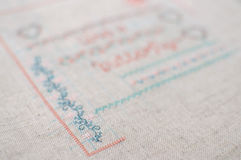 Cross-stitch embroidery on linen. Sampler with floral patterns. Royalty Free Stock Photos