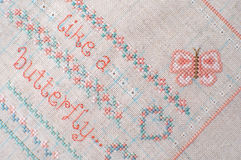 Cross-stitch embroidery on linen. Sampler with floral patterns. Stock Photography