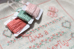 Cross-stitch embroidery on linen and three bobbins of thread. Royalty Free Stock Images