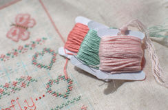 Cross-stitch embroidery on linen and three bobbins of thread. Stock Photos