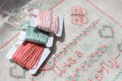 Cross-stitch embroidery on linen and three bobbins of thread. Sampler with floral patterns, hearts and butterfly. Close up. Selective focus Royalty Free Stock Photo