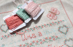 Cross-stitch embroidery on linen and three bobbins of thread. Sampler with floral patterns, hearts and butterfly. Close up. Selective focus Stock Image