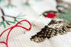 Cross-stitch embroidery and needle with red thread. Red bullfinch on a fir-tree embroidery macro close up. Stock Photos