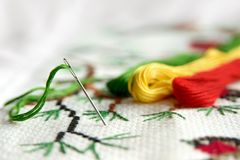 Cross-stitch embroidery and needle with red thread. Embroidery macro close up. View from above. Free copy space royalty free stock images