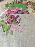 Cross stitch flowers. Using needle and thread, aida cloth embroidery needlepoint pinks and purples floral craft handmade Royalty Free Stock Photography