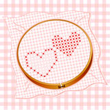 Cross Stitch Hearts. In embroidery hoop on gingham background Royalty Free Stock Image