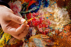 Cross-stitch. Is a popular form of counted-thread embroidery in which X-shaped stitches in a tiled, raster-like pattern are used to form a picture.  is often stock image