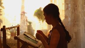 Cross stitch. A young woman embroiders sitting at the window and humming a song, sunset lighting. Side view