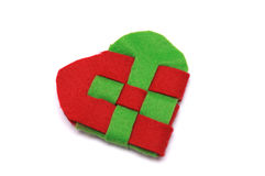 Cross stitched heart of cotton. A photo taken on a green red cross stitched heart of cotton fabric material against a white backdrop Royalty Free Stock Photo