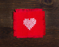 Cross stitched heart. On dark wood Stock Photography