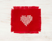 Cross stitched heart. On red Royalty Free Stock Photography