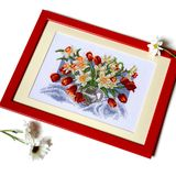 Cross stitched picture with tulips and daffodils in jug. Isolate royalty free stock images