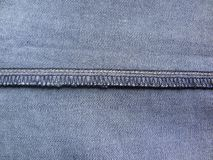 Overlocking stitch. On light blue color jeans royalty free stock images