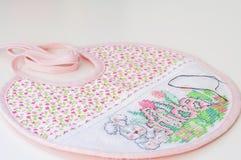 Cross stitching of a baby bib Stock Photography