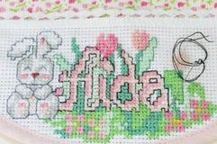 Cross stitching of a baby bib Stock Image