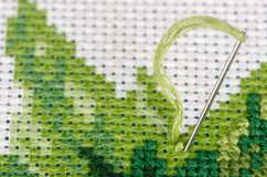 Cross stitching with a needle closeup Stock Image