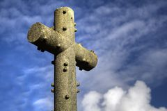 Cross stone. A stone cross with a blue sky and clouds stock image