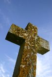 Cross of stone. Shot looking up at a stone crucifix against a blue sky for use as a Christian symbol especially at Easter time royalty free stock photo