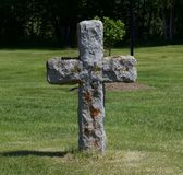 Cross of Stone. Rugged stone cross marking the final rest stop.  standing solemnly in the middle of a field weathering all times Stock Image