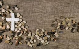 Cross of stones on wooden background for condolence or mourning Royalty Free Stock Image