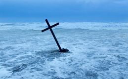 Cross In Storm. Cross Getting Pushed over in stormy waters Royalty Free Stock Photography