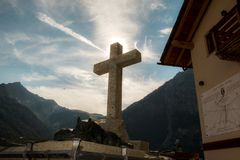 Cross with sun and mountains in background stock image