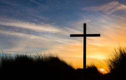 The Cross Sundown. Black cross on a hill as the sunsets behind it Royalty Free Stock Photos