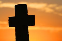 Cross at sunset. A weathered stone Christian cross silhouetted against an orange sunset Royalty Free Stock Photo