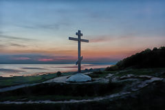Cross at sunset. Cross against a decline and coast of the lake Royalty Free Stock Image