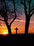 Cross at sunset. Silhouette of a cross between trees at sunset Stock Image