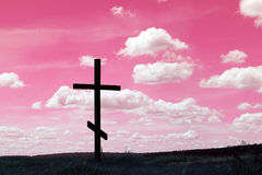 Cross symbol of christian religion against the sky. Christian Cross as symbol religion against red abstract sky background Stock Photo