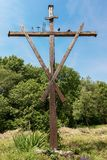 Cross with the Symbols of the Passion of Christ. Old wooden cross with the symbols of the Passion of Christ, pincer, ladder, hammer, chalice, dice, nails and Royalty Free Stock Photo