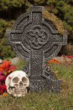Cross tomb stone with skull. A Halloween grave stone decoration Royalty Free Stock Images