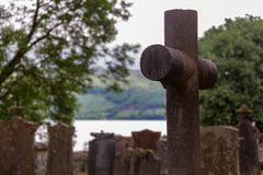 Cross and tombstones in cemetery with lake in background Royalty Free Stock Photography