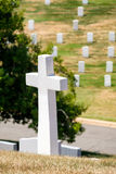 Cross and tombstones on a grassy hill at Arlington National Cemetery. Near Washington D.C Stock Images
