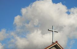 Cross on top of church, with sky and clouds behind Royalty Free Stock Image