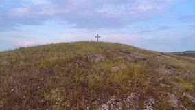 Cross on top of the hill. Low angle aerial view stock video footage