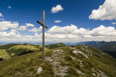 Cross on the top of a mountain with cloudy blue sky Stock Photo