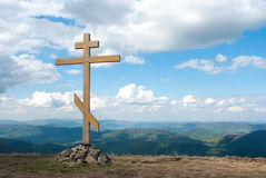 The cross on top of the mountain. Cross against the sky. Wooden cross on a hill. Christian cross. The cross on the background of m Stock Images