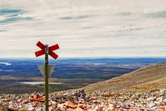 Cross On Top Of The Mountain. A sign warning about snowmobiles on top of the Yllas fjell in the Finnish Lapland. The slope is quite steep, but somebody might royalty free stock photos