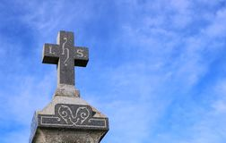 Cross on top of old gravestone with blue sky in background stock photos