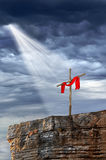 Cross on Top of Rock. Cross with cloth on rock over a stormy background Stock Photo