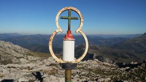 Cross touching sky. Peak of mountain basque country Stock Image